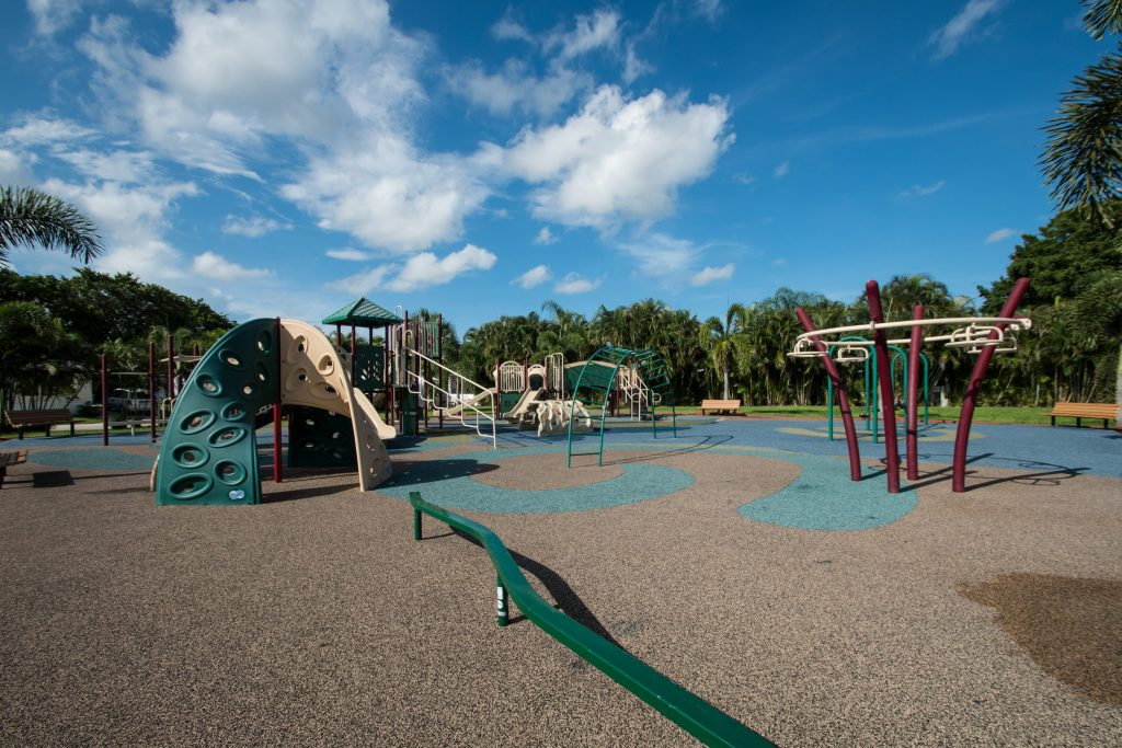 A big playground for children. There are monkey bars, slides, balance bar and swings. Bench seating is all around the perimeter of the playground. Green grass and lush trees.