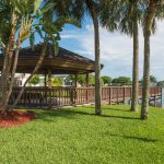 Large gazebo with covered seating at one end of dock. Lush landscape all around.