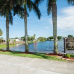 Quiet, calm waters on the lake that lap up to 5 very tall palm trees. Directional sign in front with clubhouse to the left and homes to the right well.