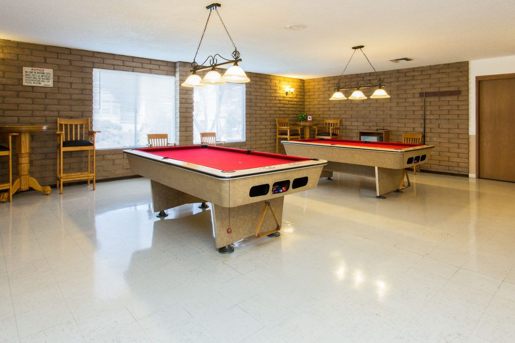 Billiards room equipped with two pool tables and seating areas. Walls lined with light brick to give a rustic feel.