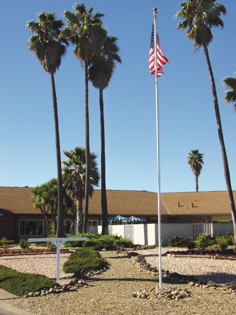Front view of the community center. Surrounded by beautiful, tall and short palm trees sitting on a bed of rocks. Well- maintained landscape with a tall raised American flag in the foreground.