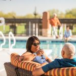 An african american couple sit in lounge seat by the pool. Woman is having a drink.