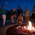 At night around the large lit fire pit, four men and two women enjoy a drink and chat while under the moon light