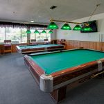 Billiards room with 2 pool tables. Seating along the wall.