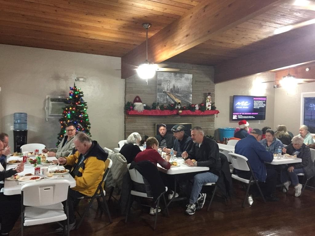 Community holiday party hosted in the community hall. 55 plus aged residents sit and enjoy dinner meals while mingling with one another. Community hall is decorated for the holidays with a Christmas tree and red and green decor over the fireplace ledge.