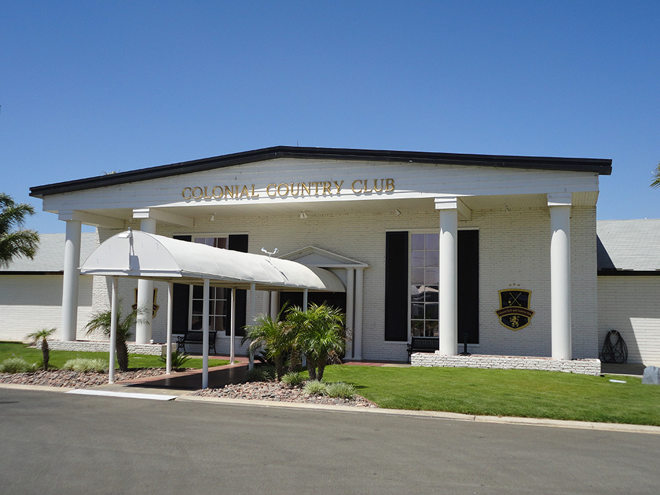 Beautiful white entrance to the country club with white pillars and black window shutters. Walkway leading to the front door is covered by an awning and surrounded by green grass on both sides.