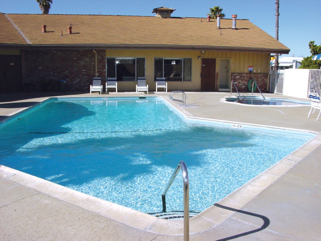 Outdoor heated pool with a large hot tub adjacent to it. Both amenities lie behind the community center, open for residents to host parties with friends and family.