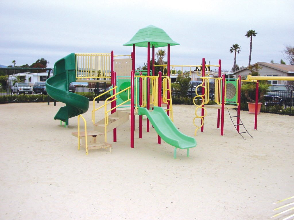 Fully equipped children's playground lying on top of a bed sand for children to play in.