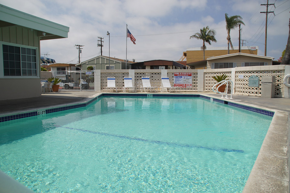 Full-size outdoor community pool enclosed by metal and beige concrete gates.