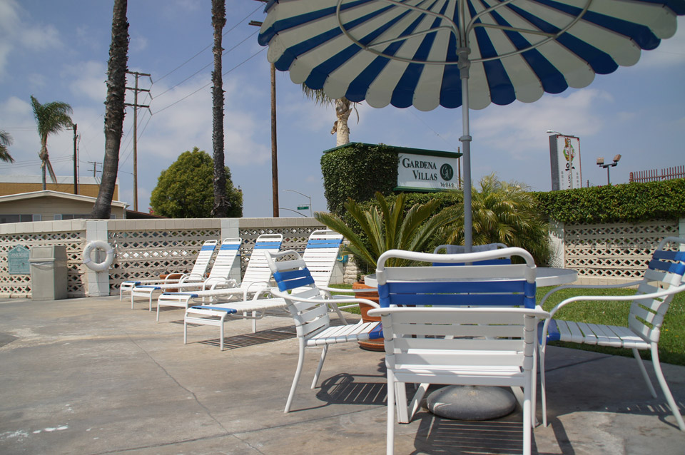 Outdoor lounge chairs for relaxation near the pool. Table with connected white and blue striped umbrella and chairs available for extra seating under the shade.
