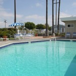Outdoor community pool available for parties and events hosted by residents. Surrounded by chairs and tables for seating.