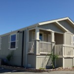 Beautiful, updated, cream colored manufactured home on corner lot. Short staircase leads to small, covered front porch.
