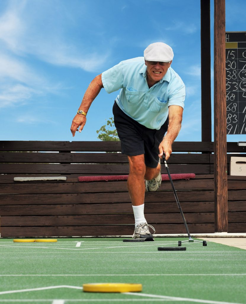 An older, retired man playing shuffleboard in black shorts, light blue polo shirt, white hat, white socks and sneakers.