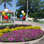 Purple and yellow flowers at front entrance with two balloon clusters of white, gold, green, red and blue balloons.