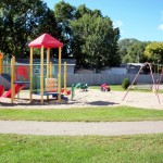 A playground area for the children with swings, slide and jungle gym.