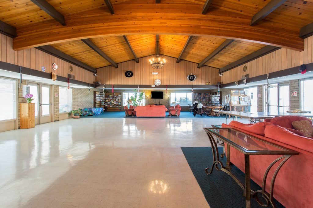 Large, open community center with high, light-wood, vaulted ceilings. Space for residents to lounge on the salmon pink couches or read a book from the novels provided.