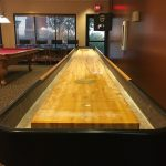 Large game room featuring indoor sawdust shuffleboard and pool table.
