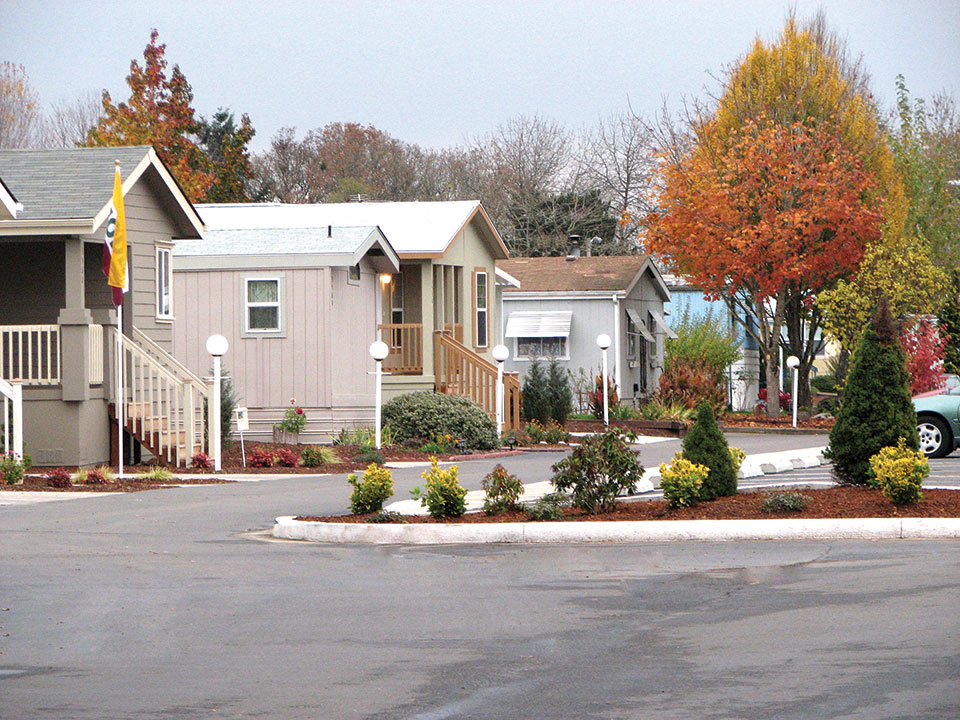 Clean paved streets in the neighborhood with row of manufactured homes. White lamppost at front of each property. Trees with fall leaves.