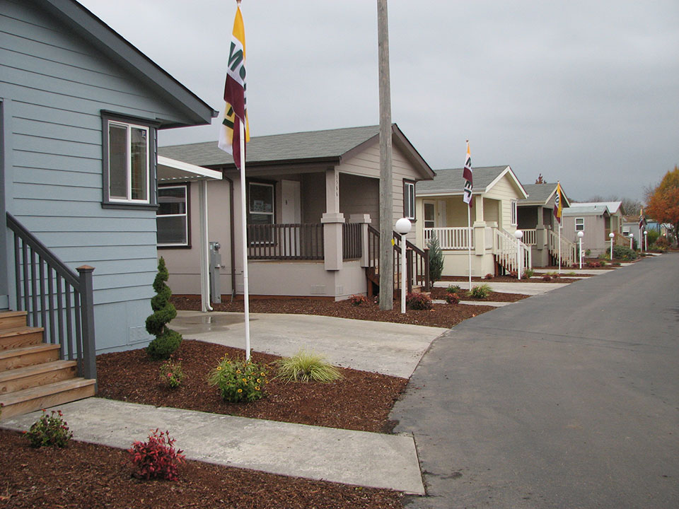 Clean paved street and manufactured homes for sale.
