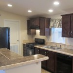 Interior view of a spacious kitchen with dark walnut cabinets, cream granite countertops, and black appliances.