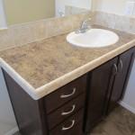 White bathroom sink surrounded by cream granite countertops, cream tile backsplash and dark walnut cabinets beneath.