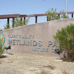 Tropicana Palms, an active 55 plus manufactured home community, is next to the Clark County Wetlands Park and Nature Center. Sign set in desert landscape.