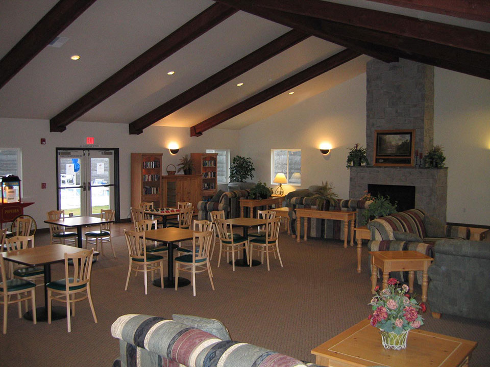 Inside community center with tables and chairs. Vaulted ceiling.