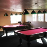Billiards and game room equipped with two pool tables for residents use.