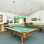 Two billiard tables within the clubhouse for residents to enjoy. Surrounded by seating and small raised tables.