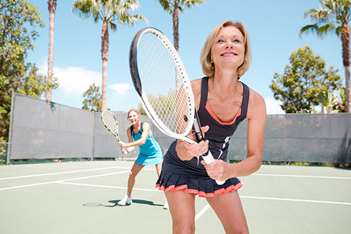 Lamplighter Village, an active 55 plus community, has tennis courts as an amenity. Two older women smile and play the game of tennis and hold their rackets ready for to hit the ball. Palm Trees in the background.