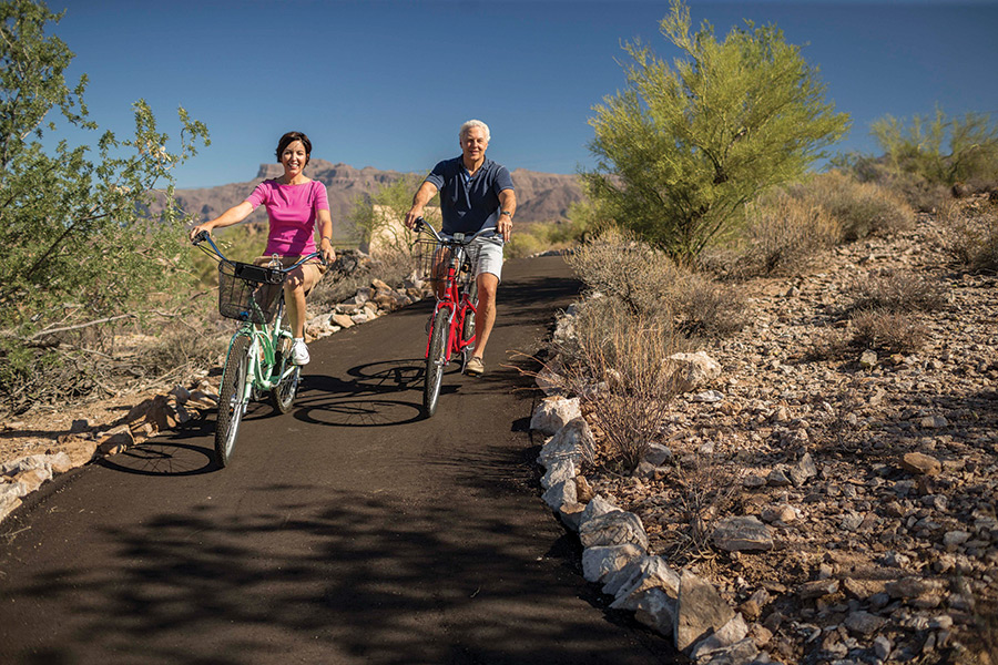 Man and woman riding bicycles along smooth path landscaped w shrubs and rocks
