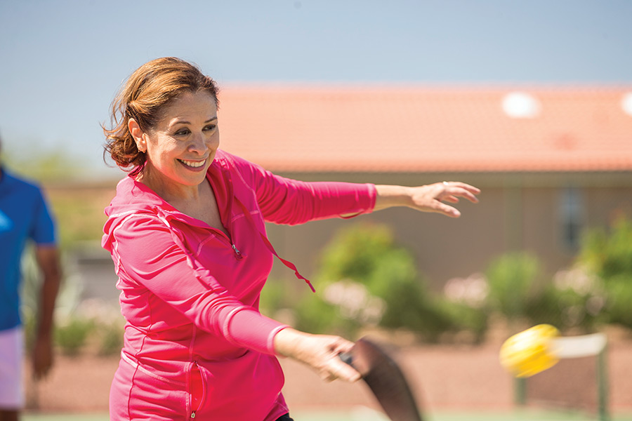Woman in magenta sweatshirt smiling while mid swing on pickleball court.