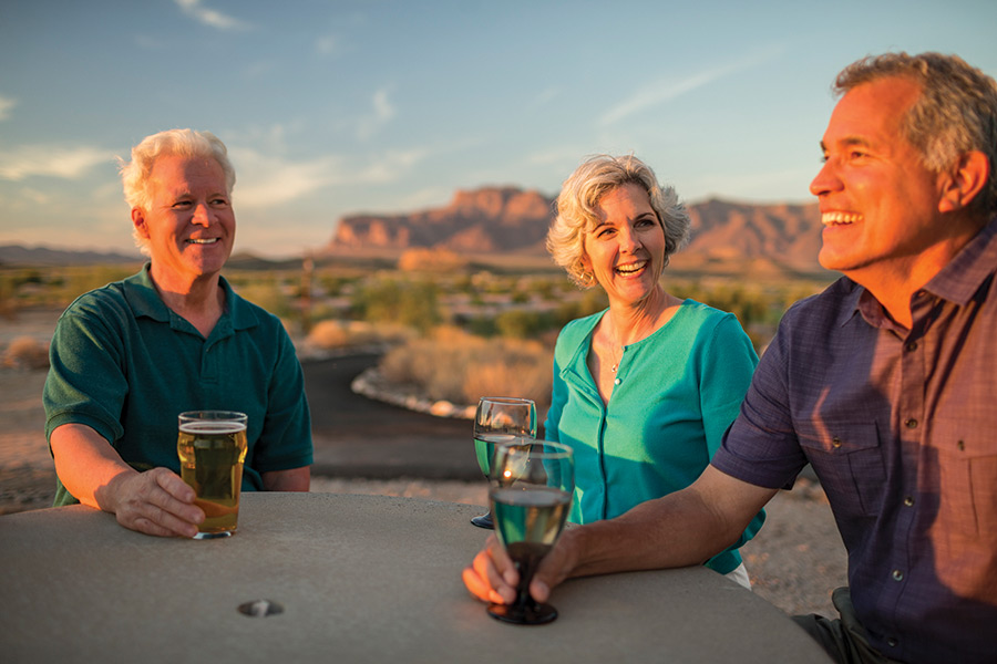 Montesa at Gold Canyon, a 55 plus community has an older woman and two older men smiling and laughing enjoying a cocktail around a table at Sunset. Beautiful Superstition mountains in background