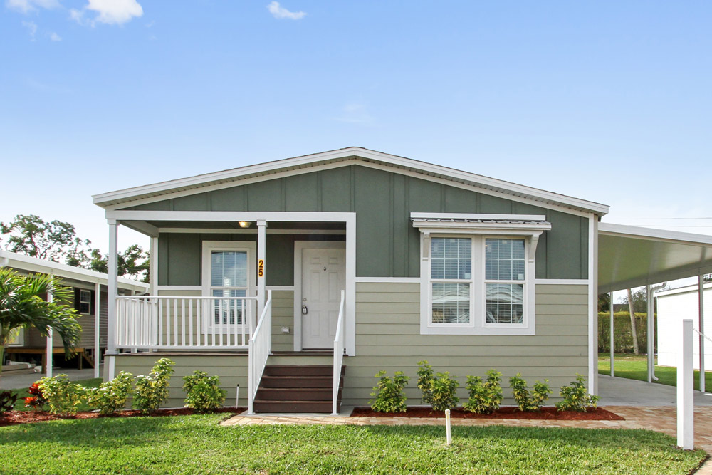 Beautiful, updated manufactured home with a well maintained landscape and freshly painted exterior. Small stairs lead up to small, covered porch with small white fencing. White front door, and window trimmings create a clean look.