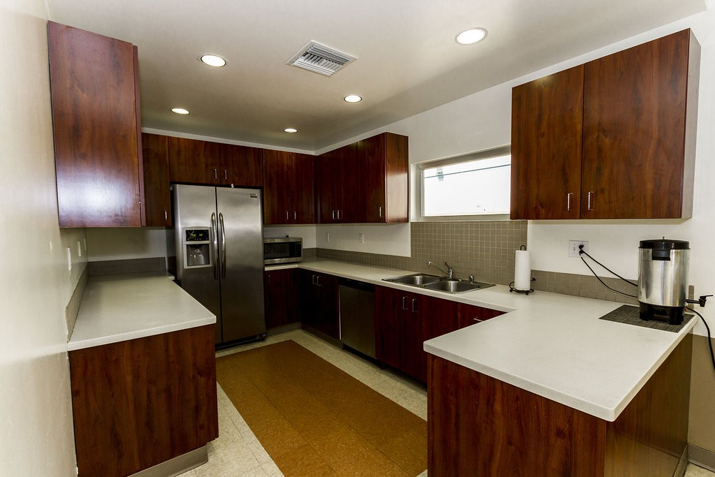 Open kitchen space within the community center with ample counter space and storage. Mahogany cabinets, white counter tops, and stainless steal fridge, sink, and microwave.