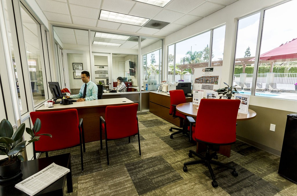 Community leasing office equipped with two different, adjacent offices. Welcoming space with a view of the community pool. Vibrant red chairs provide seating for current and potential residents.