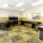 Game room including an ice hockey table, a poker table with chairs, shuffleboard table, and two arcade game systems. Small open space for residents to enjoy games with friends and families.