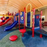 Vibrant red, blue, and yellow outdoor community playground. Covered by large steel metal carport/shelter/ shade with ample, open space for play. Rubber playground flooring throughout to ensure safety.