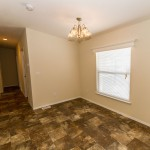 Open space within a home that can be used for a family room, dining room, or extra space. Tile flooring, and cream walls throughout with a small chandelier hanging from the ceiling. Connected is a hallway leading to additional rooms.