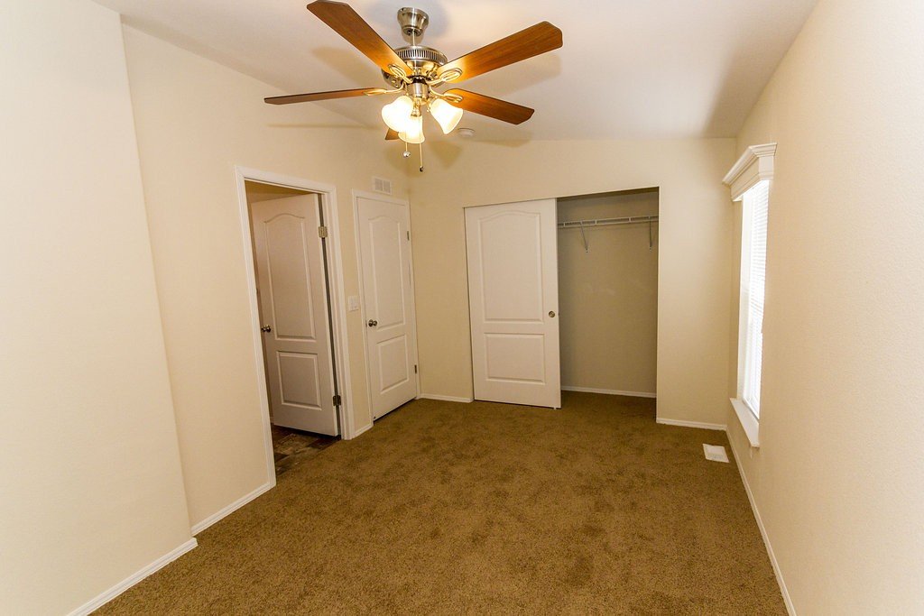 Single bedroom with tan carpet and full size closet. Ceiling fan and light hang overhead in the middle of the room, and single window allows for natural light throughout.