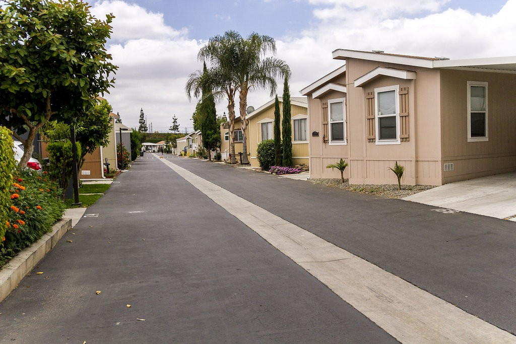 Wide, clean streets lined with well-maintained manufactured homes and landscape. Beautiful neutral colored homes and ample greenery give color to the community.