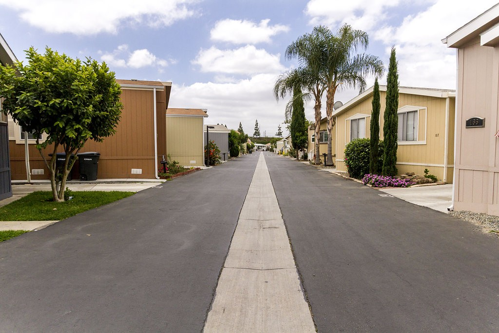 Straight view down the wide streets of Orange Mobile Home Park. Manufactured homes line both sides of the street in close proximity, creating a community feel among residents.