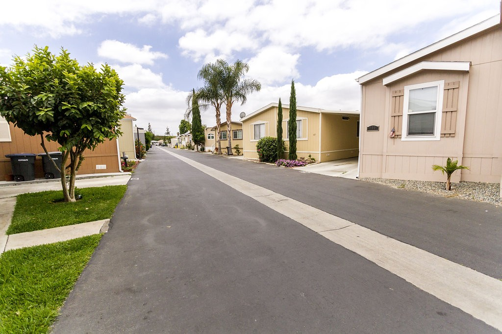Beautiful homes similar in style sit next to one another within the community. All separated by a side parking lot covered by attached carports.