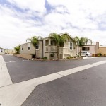 Beautiful, updated corner lot home with small staircase leading up to a covered porch. Cream colored all around with white shutters on the windows. Aesthetically pleasing with well maintained landscape and palm trees around the home.