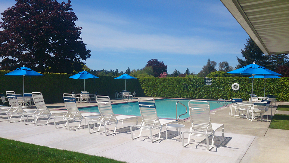King Village, an all age manufactured home community, has swimming pool with lounge chairs, tables, and blue patio umbrellas.