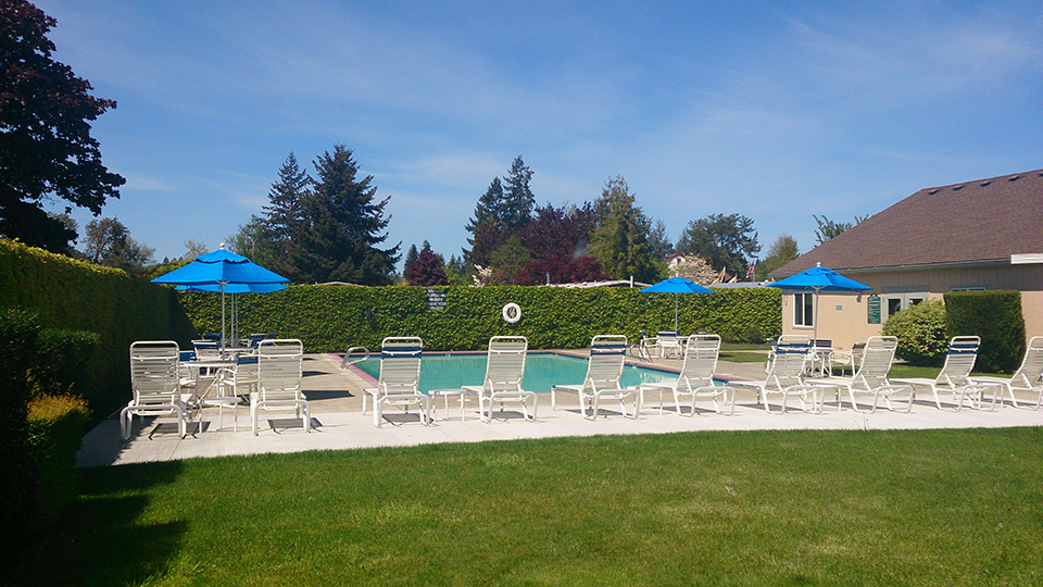 Swimming pool with lounge chairs, tables and blue umbrellas set up.