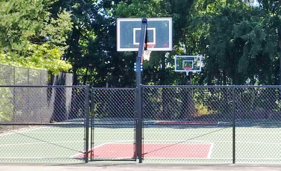 New outdoor basketball court with shaded trees in the background.