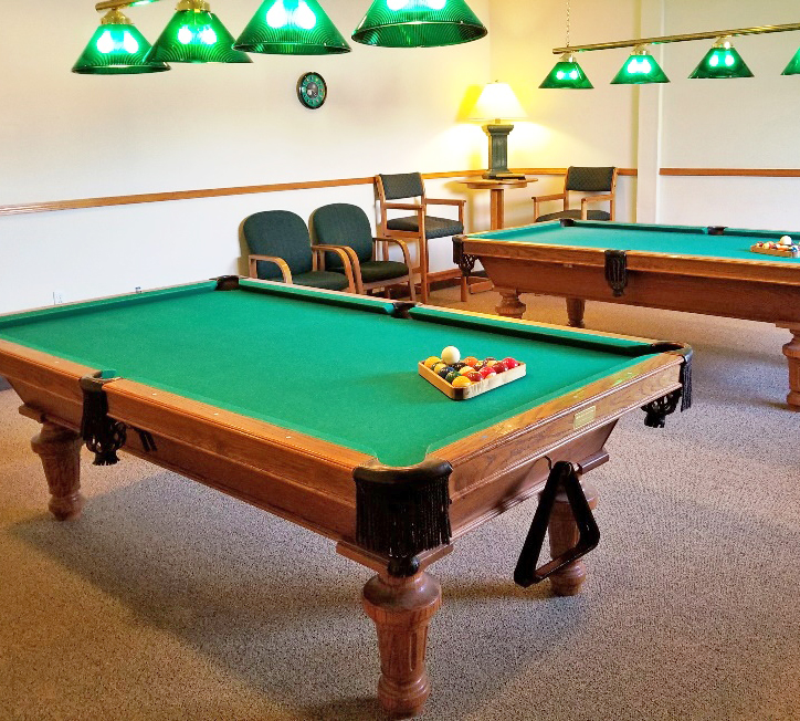 A billiards room with two pool tables with lighting above the tables.