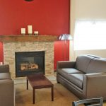Renovated community room with fireplace and mantel. Leather loveseats to sit on. Orange accent wall around fireplace.