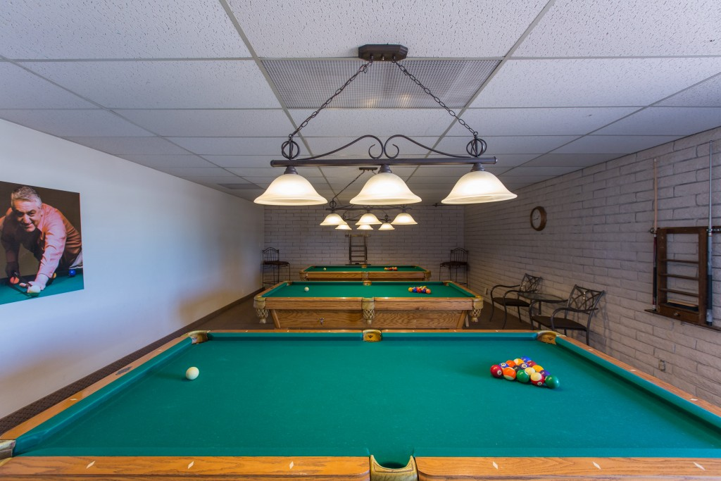 A billiards room with 3 pool tables and seating.